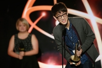 """Hyungjik Lee of Florida State University accepts his award in the Children's Program category for """"Lemonopolis"""" at the 35th College Television Awards as presenter Lauren Potter looks on."""